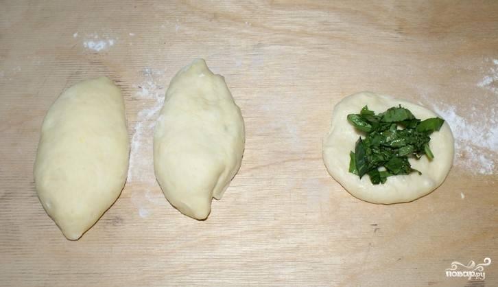 2. Щавель помоем, измельчим и смешаем с оставшимся сахаром. Из теста сделаем лепешки, внутрь каждой кладем начинку. Формируем пирожки.
