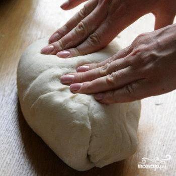 Тесто выложить на стол, посыпанный мукой, и месить его руками до тех пор, пока оно не станет эластичным. Далее дать полежать тесту около 10-15 минут, накрыв пленкой или полотенцем.