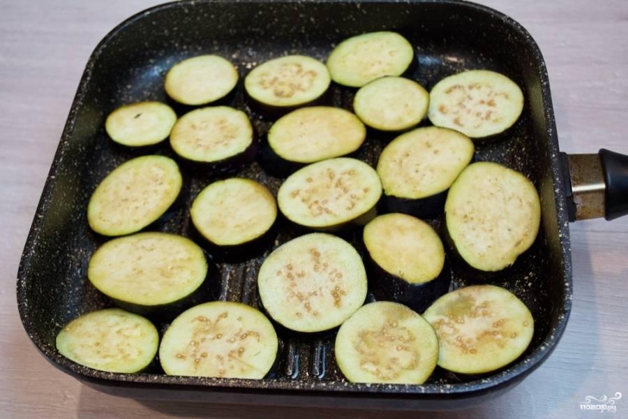 Для приготовления баклажан я буду использовать сковороду гриль. Сковороду разогрейте хорошо. Капните на сковороду немного растительного масла. Смажьте сковороду растительным маслом при помощи кисточки. На горячую смазанную сковороду выложите бакладыновые кружочки. Обжарьте с двух сторон по 2-3 минуты с каждой стороны, до появления румяных полос на овоще.