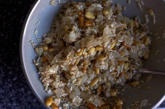 Разогрейте на сковороде масло и быстро обжарьте орешки, затем откиньте их на дуршлаг. На оставшемся масле обжарьте порезанные лук и чеснок. Половину лука и чеснок смешайте с орешками и промытым рисом для начинки.