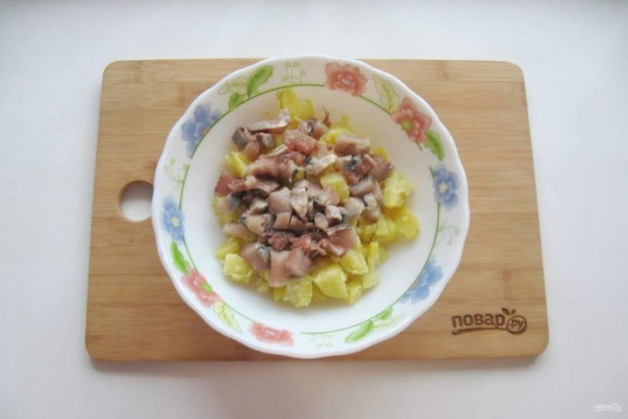 Филе сельди также мелко нарежьте и добавьте в картофель.