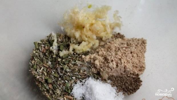 3.Для маринада в миске смешиваем соль, травы, имбирь, перец и несколько пропущенных через пресс зубчиков чеснока.