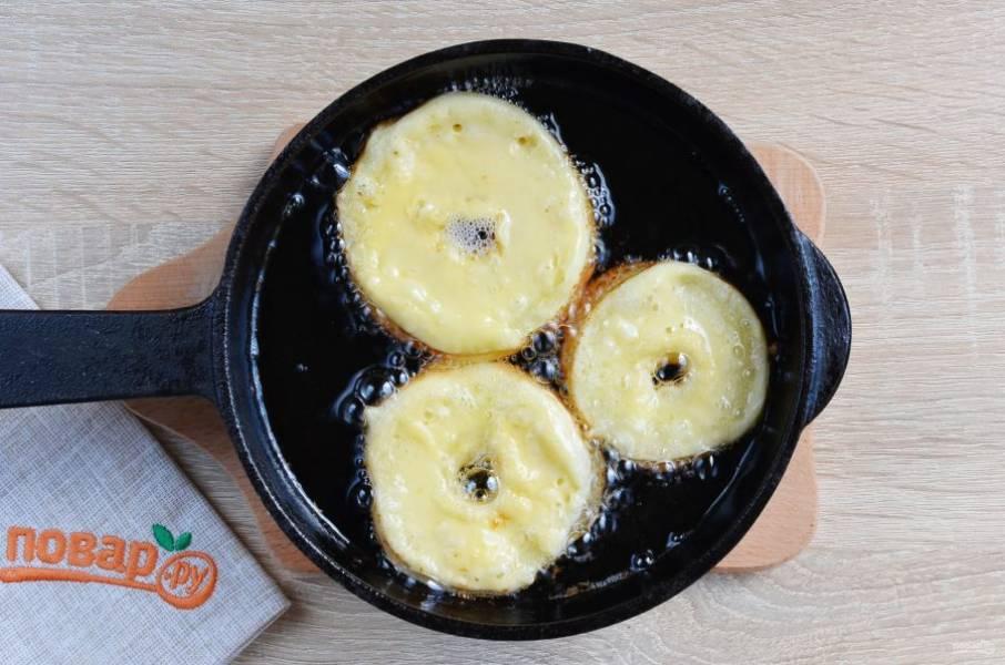 Сразу кладите яблочные колечки в горячее масло. Учитывайте, что пончики немного подрастут, чтобы они не слиплись, нужно соблюдать дистанцию между ними. Когда я фотографировала, они уже успели подрасти и подрумянится с нижней стороны.