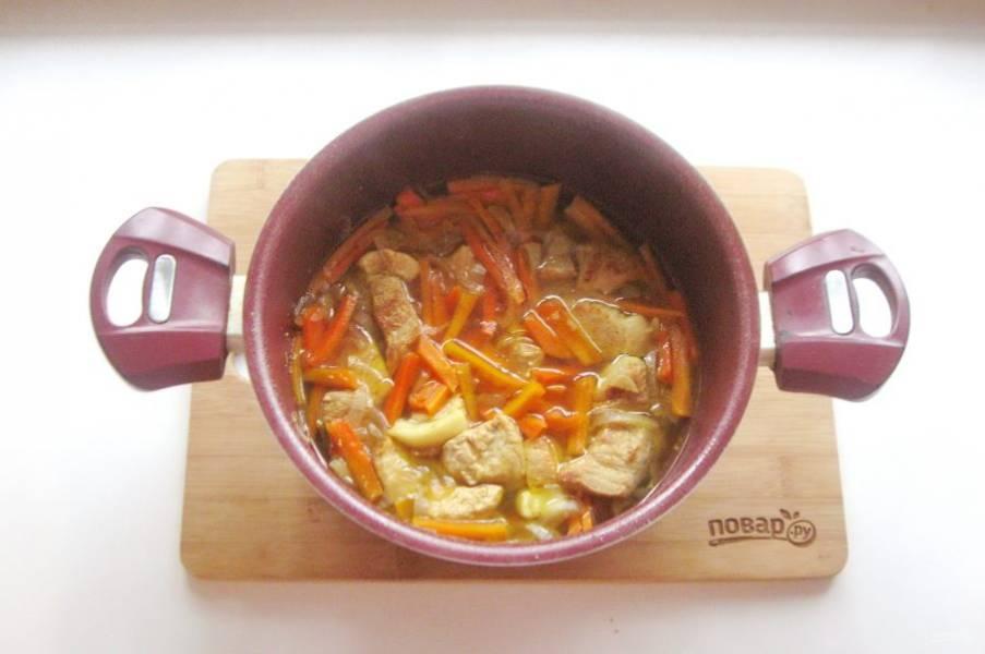 Накройте кастрюлю крышкой и тушите свинину с овощами в масле 10-15 минут, периодически перемешивая. После налейте 300-350 мл. воды, добавьте молотую куркуму, соль по вкусу и тушите мясо до готовности.