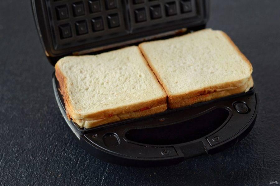 Разогрейте вафельницу. Переложите бутерброды, накройте и выпекайте 5-7 минут.