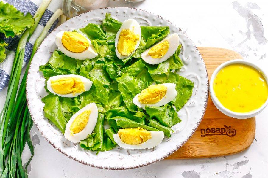 Промойте листья салата, обсушите их бумажным полотенцем и нарвите руками на тарелку. Отварные яйца очистите от скорлупы, промойте в воде и нарежьте на четвертинки. Выложите на зелень.