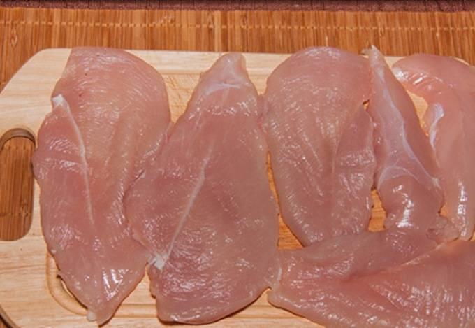 Куриное филе разрежьте на плоские куски, накройте пленкой и аккуратно отбейте.
