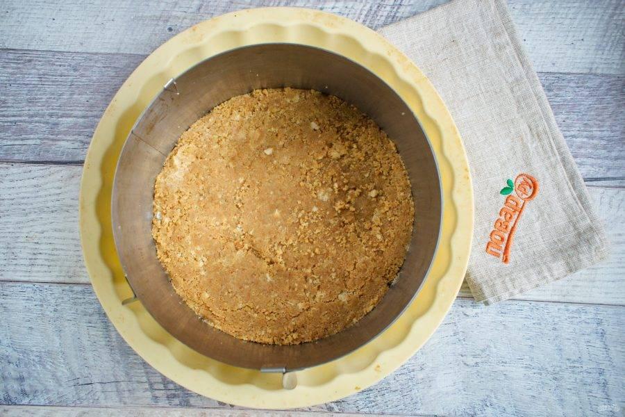 Распределите крошку из печенья по дну разъемной формы (диаметр 18 см), утрамбуйте. Отправьте запекаться в духовку на  10 минут при 180 градусах.