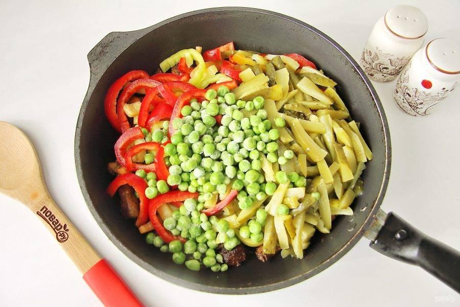 Когда мясо будет полностью готово, добавьте к нему нарезанные соломкой огурцы и перец. Добавьте горошек. Горошек может быть свежий, замороженный или даже консервированный.