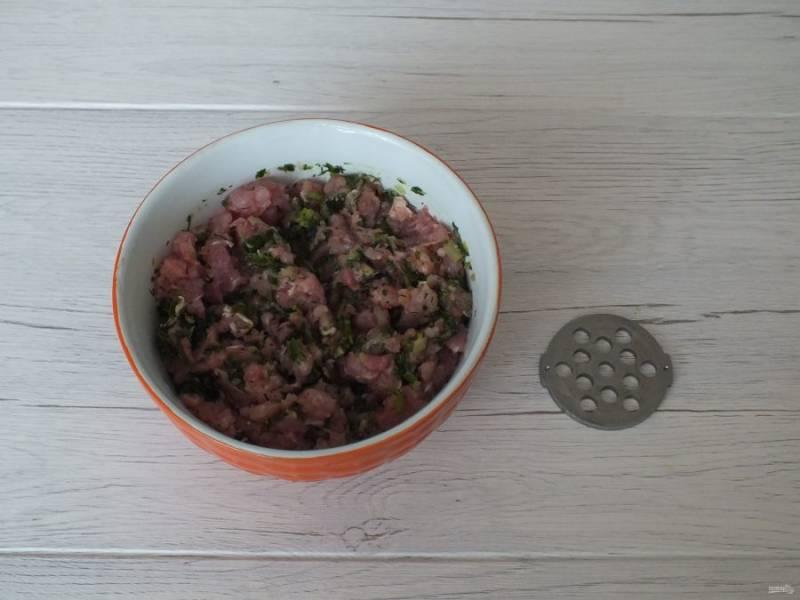 Мясо индейки перекрутите на мясорубке с крупной решеткой. Добавьте чеснок и зелень.