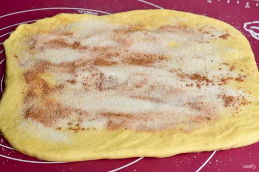 Раскатайте тесто в пласт, посыпьте его сахаром и корицей.