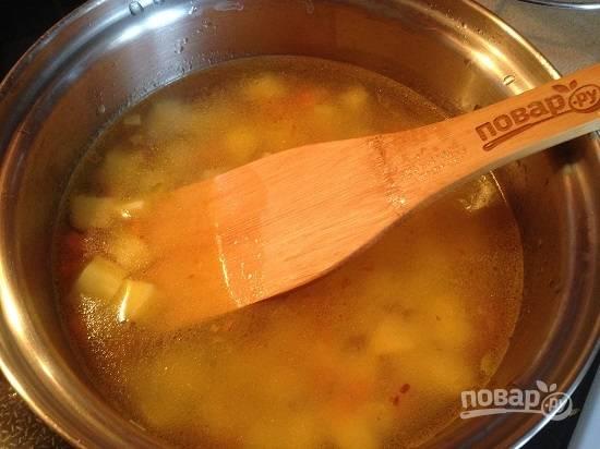4. В кастрюлю к обжаренным овощам наливаем бульон или воду и добавляем картофель. И варим минут 10 после закипания. Солим и перчим.