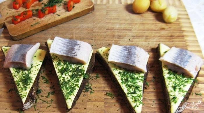 Выкладываем на край каждого бутерброда кусочек сельди.