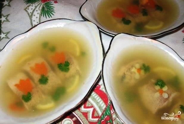 Заранее отварите и нарежьте морковь. Куски рыбы разложите по тарелкам. Залейте до половины объёма бульоном. Украсьте блюда морковью, зеленью, лимоном. Полностью остудите блюдо. Потом долейте бульон и оставьте в холодильнике. Приятного аппетита!
