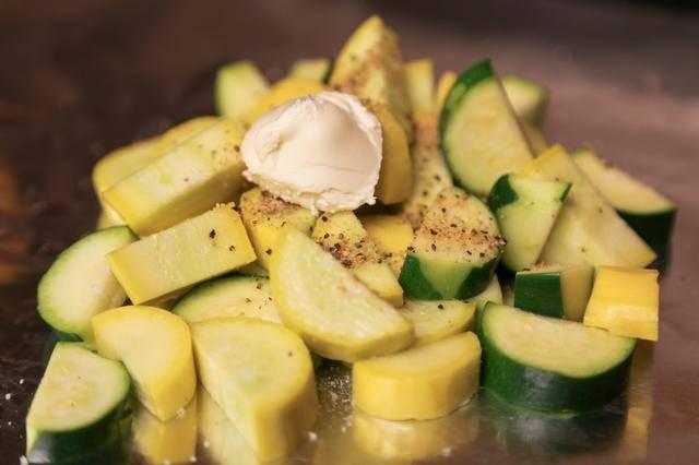 4. Небольшое количество кабачков выложить на лист фольги. Посолить и поперчить по вкусу. Чеснок очистить и пропустить через пресс. Добавить немного в каждую порцию. При желании можно отдельно перемешать кабачки со специями, а затем выложить на фольгу. Также можно добавить любимые специи, сушеные травы или измельченную свежую зелень. Сверху выложить небольшой кусочек сливочного масла, чтобы кабачки в фольге в домашних условиях были сочнее.