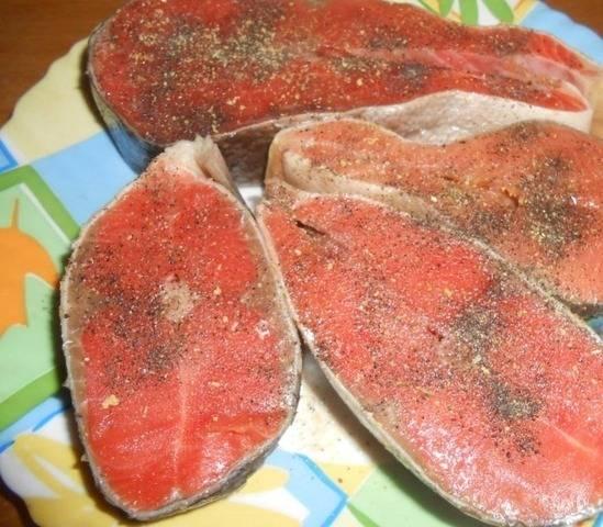 Чистим рыбу, нарезаем её на части (стейки). Натираем каждый кусочек рыбы смесью соли, перца и специй.