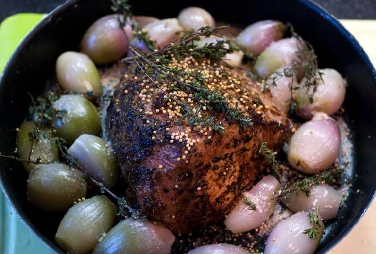 Обжаренное мясо перекладываем в форму для запекания, а вокруг него раскладываем лук-шалот, наливаем в форму немного водички. Затем посыпаем луковицы темным сахаром, а на телятину выкладываем зерна горчицы и веточки тимьяна. Ставим форму в духовку, разогретую до 200 градусов, запекаем мясо 40-50 минут. Где-то через 20 минут после того, как поставили мясо в духовку, нужно аккуратно перевернуть лук в форме на другую сторону, иначе он пригорит. Когда мясо будет готово, даем ему минут 10-15 постоять в выключенной духовке, а затем вынимаем телятину и подаем ее к столу. Приятного аппетита!