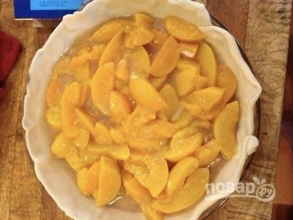Персики процедите от жидкости, в которой они находились, и выложите в емкость. Добавьте к ним корицу, соль, сахар и кукурузный крахмал. Перемешайте и выложите аккуратно на тесто.