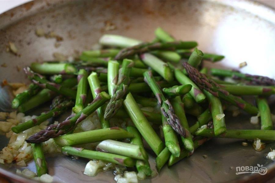 3.Очистите лук и нарежьте его мелко, измельчите чеснок. Разогрейте сковороду с растительным маслом и выложите лук с чесноком, обжаривайте пару минут. Нарежьте спаржу небольшими кусочками и добавьте ее к мягким овощам в сковороде, готовьте еще пару минут.