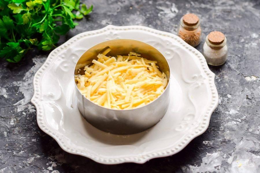 Твердый сыр натрите на мелкой или средней терке. Выложите сыр поверх белков, смажьте майонезом.