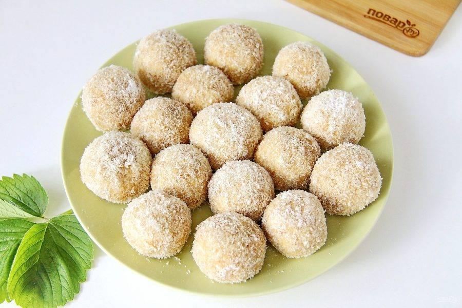 Все шарики обваляйте в кокосовой стружке, переложите на блюдо и уберите в холодильник на 30 минут.