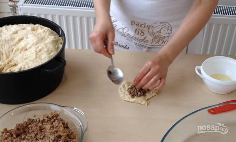 11.Наше тесто очень хорошо подошло, отщипывайте от него небольшие кусочки. Стол смажьте растительным маслом, каждый кусочек руками распределяете на столе, внутрь кладете 1 столовую ложку начинки, защипните края.