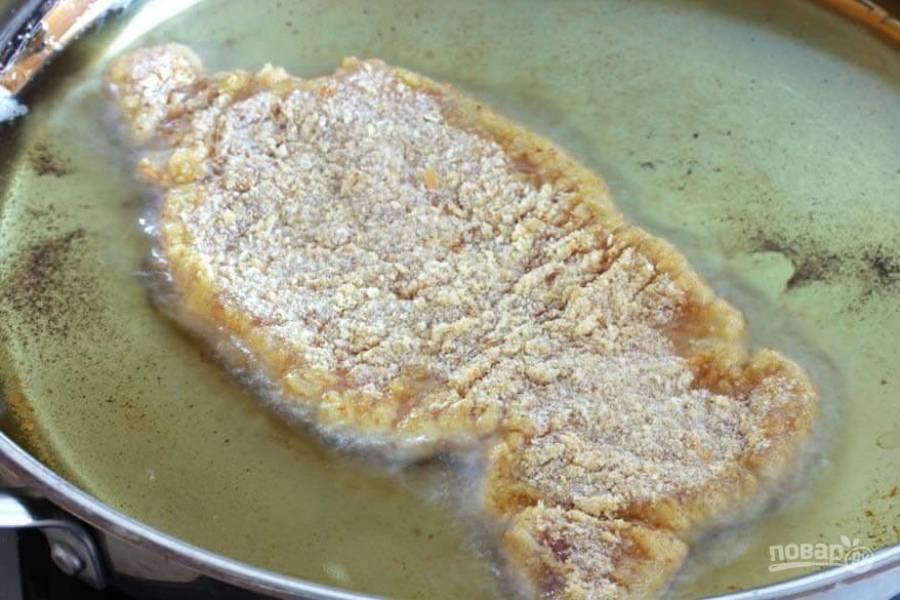 Разогрейте большое количество масла в глубокой сковороде. Выложите туда шницель.