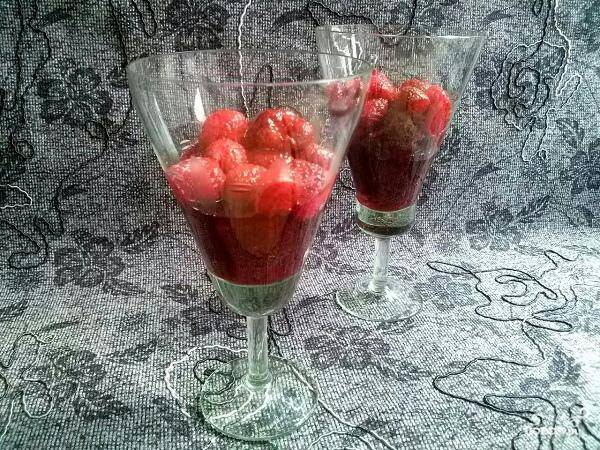 Налейте сверху бисквита клубничный сироп, затем выложите ягоды.