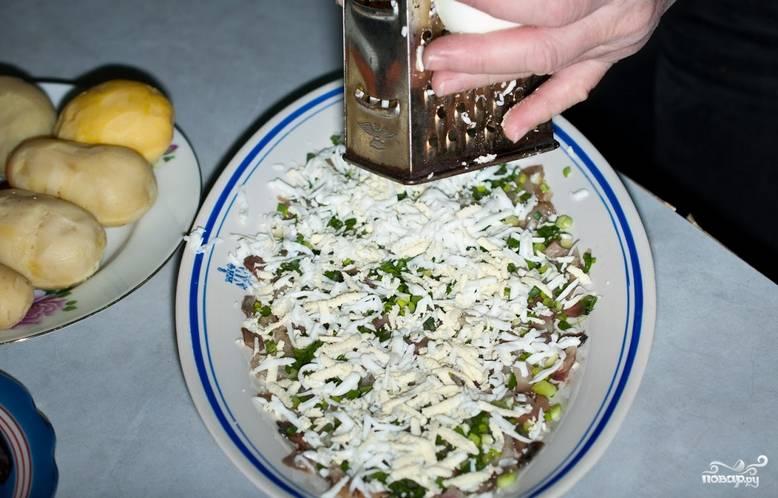 Вареные яйца очищаем, трем на терке и присыпаем сельдь с луком.