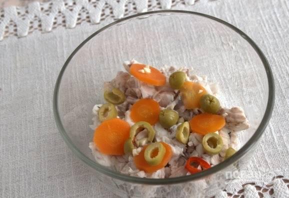 В презентационное блюдо выложите измельченную треску, несколько колечек моркови и перчика чили, пропущенный через пресс чеснок и нарезанные оливки.