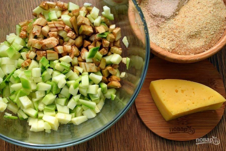 Баклажан очистите. Если у кабачка жесткая кожура, также снимите ее. Нарежьте овощи мелкими кубиками (по 5 мм), посолите, дайте постоять 5 минут. Отожмите лишнюю жидкость.