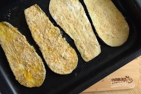 Обваляйте ломтики баклажана в муке, окуните во взбитые яйца и обваляйте в панировочных сухарях. Выложите на противень, смазанный оливковым маслом.