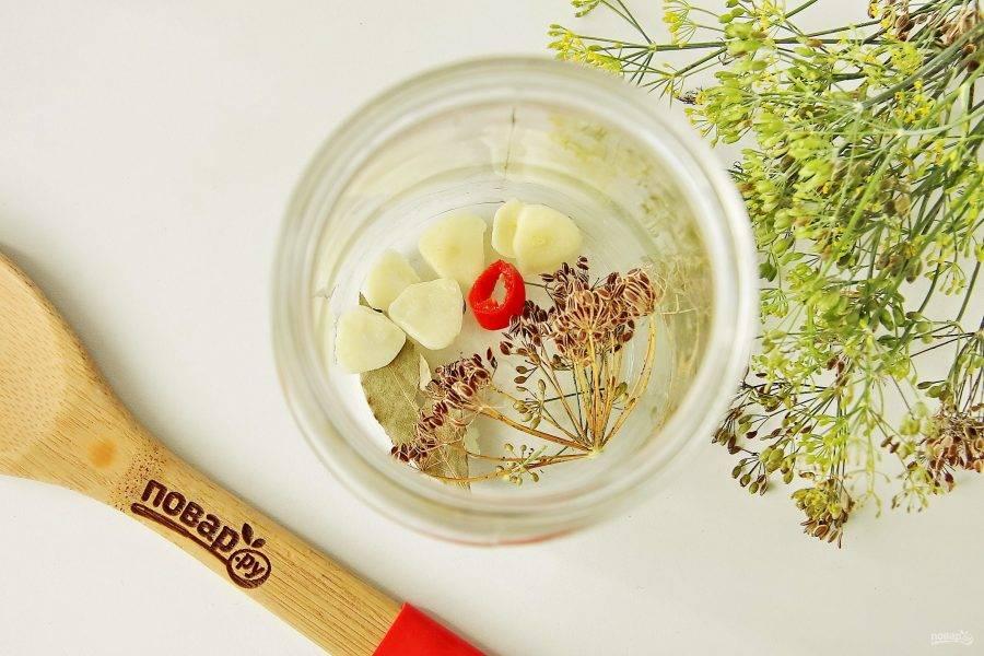 Банки простерилизуйте любым привычным способом. На дно уложите укроп, лаврушку, перец горошком, гвоздику, нарезанный чеснок и колечко горького перца.