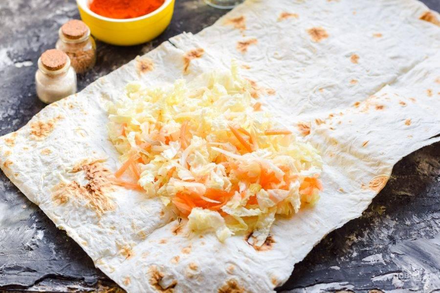 Разложите лаваш на рабочей поверхности. Поверх выложите нарезанную пекинскую капусту и натертую морковь.