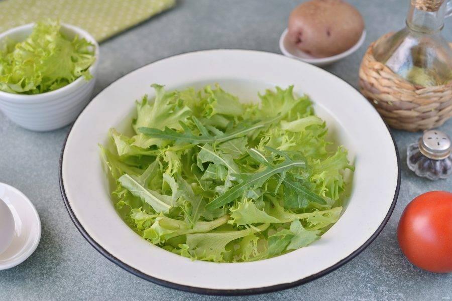 Помойте и обсушите салатные листья и рукколу. Латук можно слегка порвать руками, выложите его и половину рукколы на тарелку.
