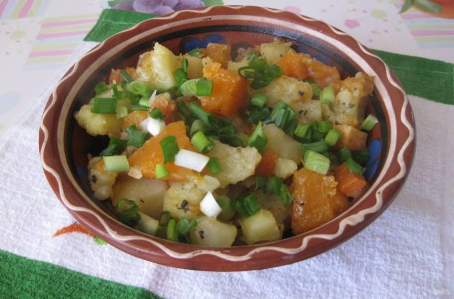 Добавьте соль и перец по вкусу, а также люьимые приправы по желанию. Тушите блюдо под крышкой около 20 минут до мягкости тыквы и картошки. Подавайте, присыпав измельченным зеленым луком.