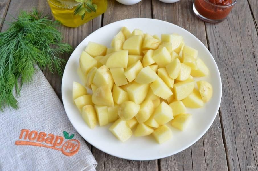 Пока овощи зажарятся для заправки борща, очищенный картофель порежьте небольшими кусочками и бросьте вариться в кипящий бульон. Варите 15 минут.