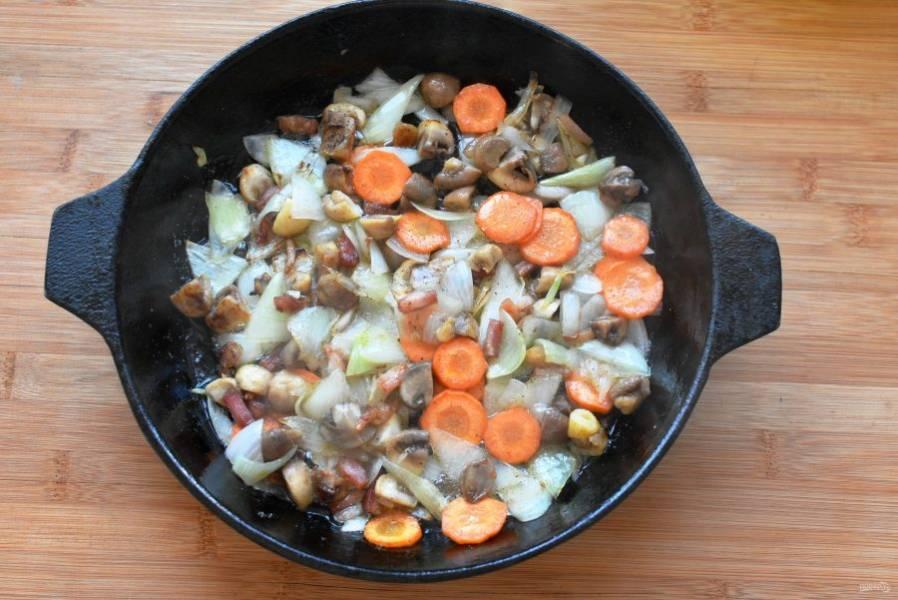 Добавьте в сковороду кружочки моркови и крупно порезанные шампиньоны. Жарьте до мягкости, помешивая.