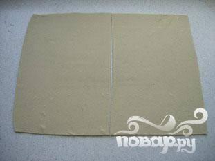Раскатать слоеное тесто  в большой прямоугольник, затем разрезать на 2 равные части.