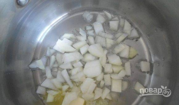 В кастрюле с толстым дном разогрейте всё масло. Обжарьте в нём нарезанный кубиками лук.