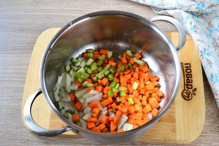 Лук, морковь и сельдерей порежьте на небольшие кубики, сложите в кастрюлю с разогретым растительным маслом и обжарьте в течение 3-5 минут.