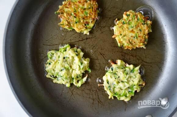 3.Разогрейте сковороду с оливковым маслом, ложкой выложите кабачковую смесь и обжаривайте до готовности с двух сторон, переложите их сразу на салфетку.