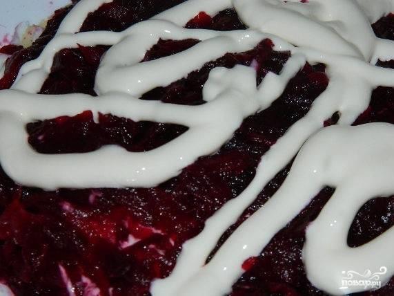 5.Приступайте к оформлению блюда. Первым слоем выложите охлажденную свинину. Нанесите майонезную сетку. Прикройте тертым сыром. Следующий слой – тертые яйца. Накройте измельченной на терке морковью. Смажьте майонезом. Прикройте слоем тертой свеклы. Посолите, нанесите майонезный рисунок.