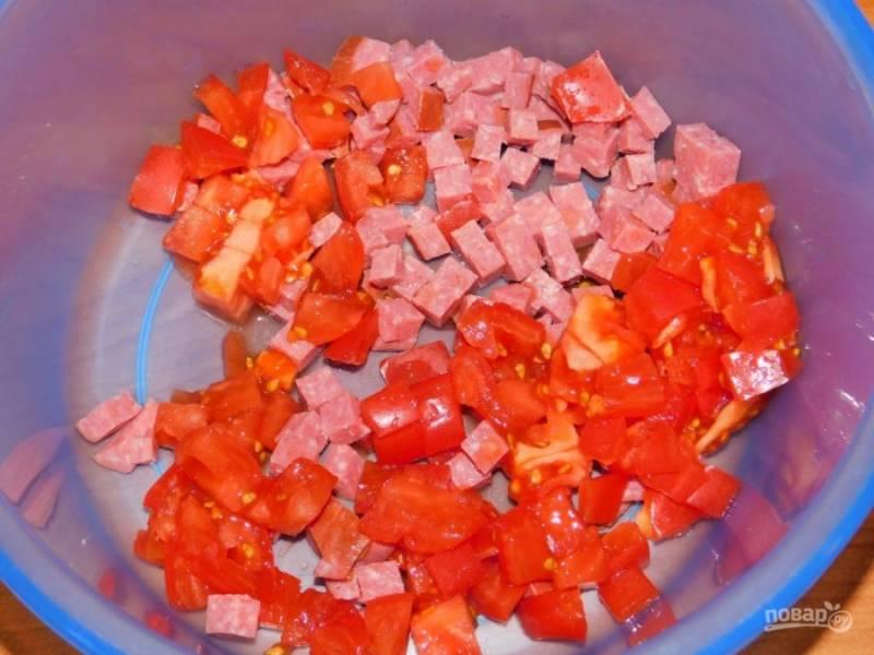 Нарежьте кубиками колбасу и помидоры.