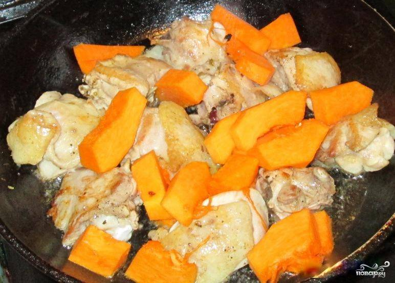 Пока бедра жарятся, займитесь тыквой. Промойте ее и очистите от всего лишнего (кожуры, семечек). Нарежьте тыкву небольшими кусочками, выложите на сковороду с курятиной.