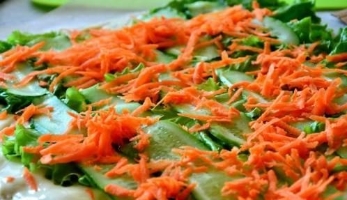 Морковь натрите и ровным слоем выложите на огурец.