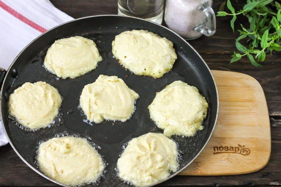 Прогрейте растительное масло в сковороде и выложите в него столовой ложкой порции теста. Сразу же убавьте нагрев до минимального и обжарьте сырники по 1-2 минуте с одной стороны.