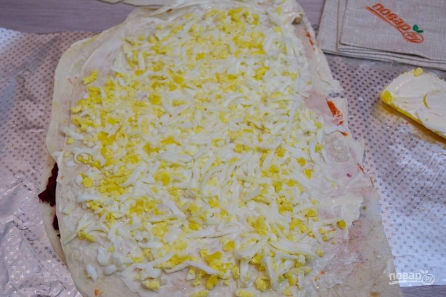 Натрите на терку отварные яйца. Выложите на лаваш и распределите. Накройте новым листиком лаваша. Ни один из слоев я не солила. У меня достаточно соли в майонезе и селедке. Если вам мало, посолите по вкусу каждый слой.