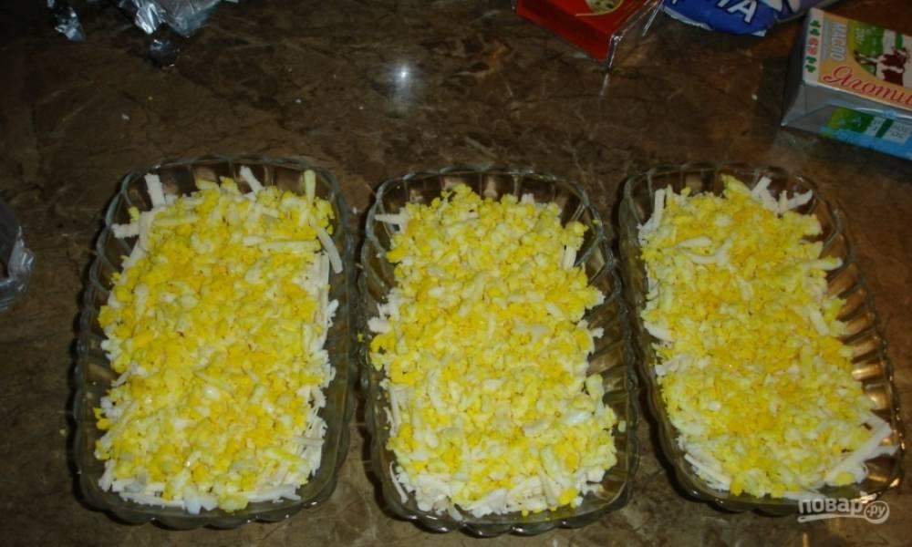 2. Отварные яйца натираю на крупной терке (не отделяю желтки от белков) и укладываю поверх плавленого сыра.