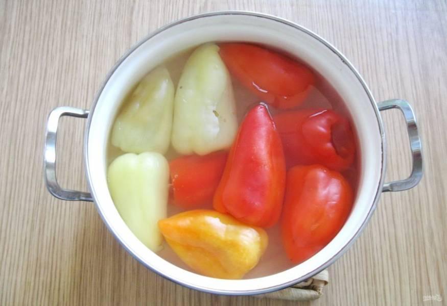 В кастрюлю налейте воду, доведите её до кипения и выложите перцы, накройте кастрюлю крышкой. Варите перцы с момента закипания 3-4 минуты. Когда они изменят цвет, достаньте из кастрюли.